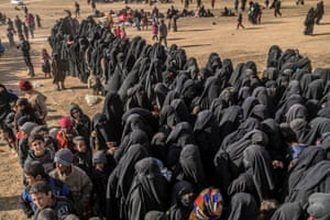 Civilians evacuated from the Islamic State (IS) group's embattled holdout of Baghouz wait at a screening area held by the US-backed Kurdish-led Syrian Democratic Forces (SDF), in the eastern Syrian province of Deir Ezzor,
