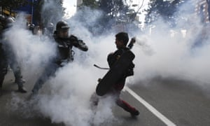 A protester charges a police officer with a gas canister before the start of a bullfight in Colombia.