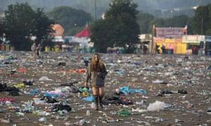 A reveller picks her way through discarded litter at the Glastonbury Festival onJune 29, 2015.