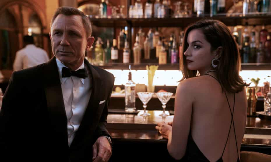 James Bond in a dinner jacket and Paloma in an evening dress standing together at a bar, looking at something off camera