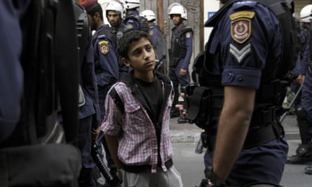 Bahraini police arrest a boy during anti-government protests in the capital of Manama in 2013.