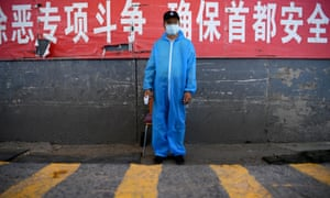 A security guard wearing a protective mask and suit stands at a checkpoint at the Xinfadi market in Beijing on 14 June 2020.