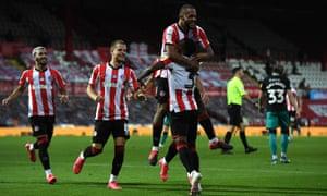 Bryan Mbeumo celebrates scoring Brentford's third goal with teammate Rico Henry.