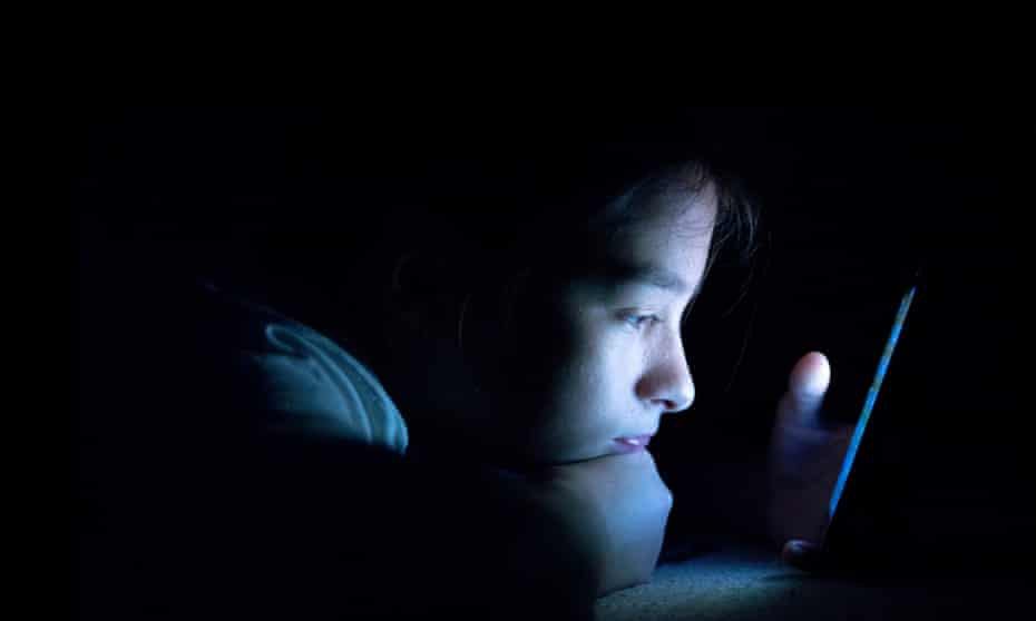 Teenager on her smart phone in her bed
