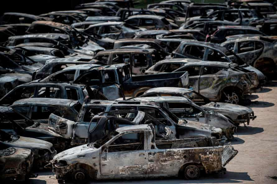 Burnt cars parked outside a football stadium following a wildfire at the village of Rafina, near Athens