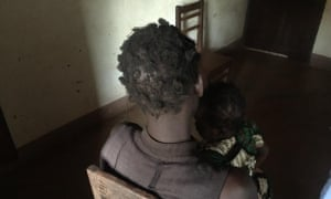 A woman holds her two-year-old daughter, fathered by a Ugandan soldier