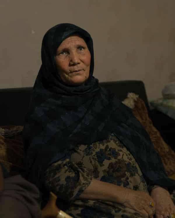 Durdana (65) with her family sits on a sofa in a smugglers house in the centre of Van, Turkey 2021.