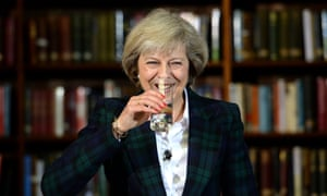 Theresa May smiling and drinking a glass of water