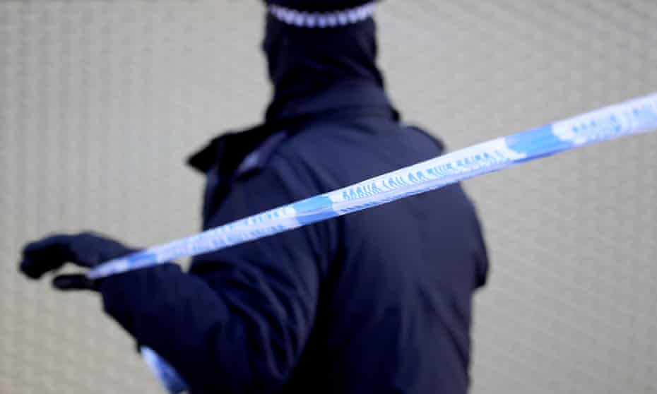 policeman unrolls crime scene tape