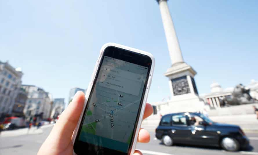 The Uber app and a black cab in London