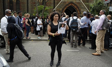 A woman holds up a photograph of missing child Jessica Urbano near the scene of the fire in Grenfell Tower.