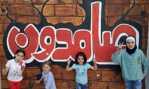 Children at school in Aleppo under a sign saying 'still standing'.