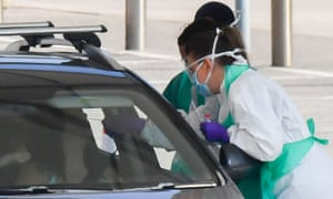 Medical staff wear PPE as they test a NHS worker at a drive-through Covid-19 testing facility in Rochdale.