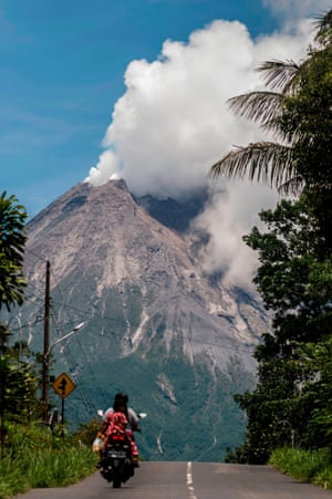 Villagers commute on a road as Indonesia's most active volcano, Mount Merapi, spews rocks and gas in Yogyakarta