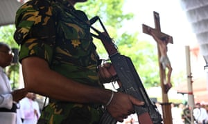 A soldier stands guard during a funeral service at St Sebastian's church in Negombo