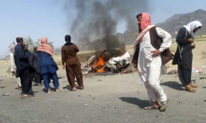 residents gather around a destroyed vehicle hit by a drone strike in which Mansoor was believed to be travelling.