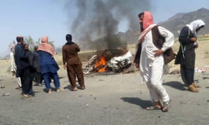 Local residents gather around a destroyed vehicle hit by a drone strike in which Mullah Akhtar Mansoor was believed to be travelling