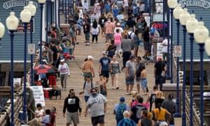 Few people wear masks or keep their distance as they walk on the Oceanside, California, last week.