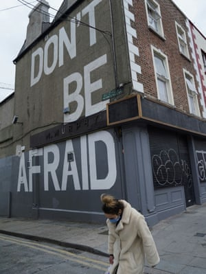 """Dublin, IrelandA woman wearing a protective face mask walks past a building with the message """"Don't be afraid"""" written on it as the spread of coronavirus disease continues."""