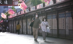 People wearing masks walk in a street in Asakusa, Tokyo, Japan, 24 May 2020.