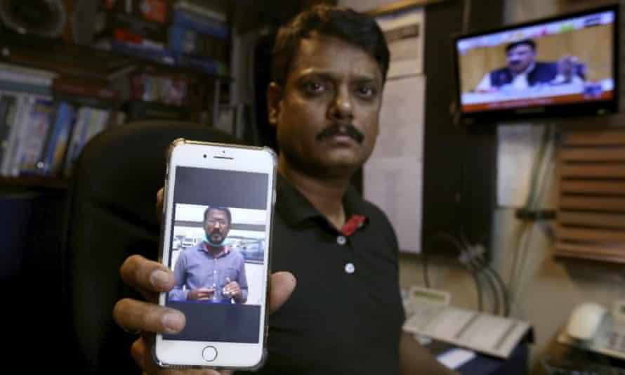 Fahim Siddiqi, Karachi bureau chief of Geo News, shows a picture of his missing colleague, Ali Imran Syed.