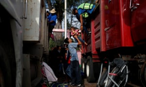 A migrant helps a girl get off a truck as they hitch a ride from Santo Domingo Ingenio to Matías Romero Avendano on 8 November.