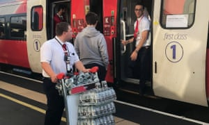 An LNER staff member provides bottled water for passengers stranded at Peterborough station.