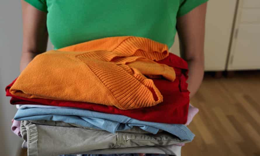 Woman holding pile of clothes