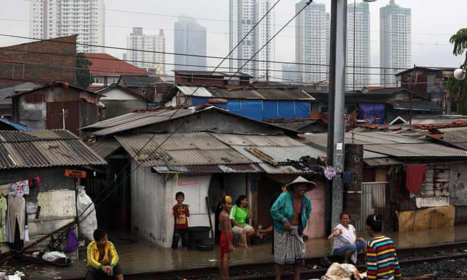 People rest around the railway track near their flood-affected houses in the Tanah Abang slum area in Jakarta, Indonesia.