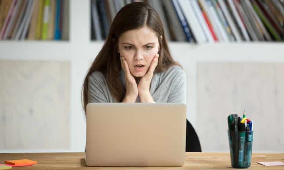 Frustrated woman looks at a computer screen