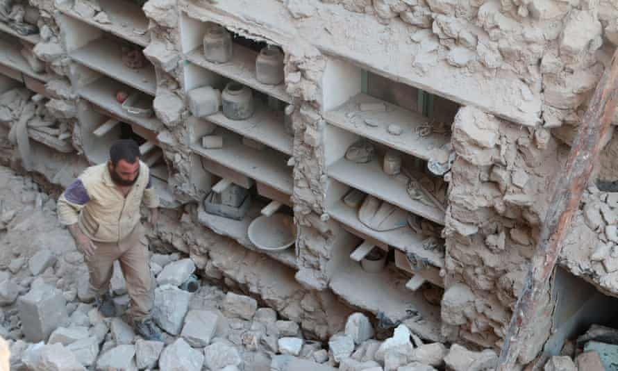 A civil defence member looks for survivors amid rubble of damaged houses after an airstrike on rebel-held Old Aleppo.