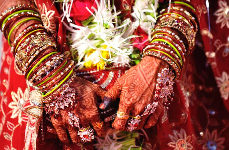 An Indian bride with henna-decorated hands waits to participate in a mass marriage
