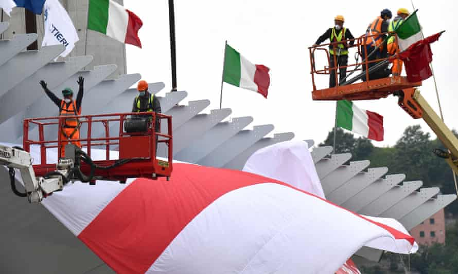 Construction workers install the final span of the new motorway bridge in Genoa