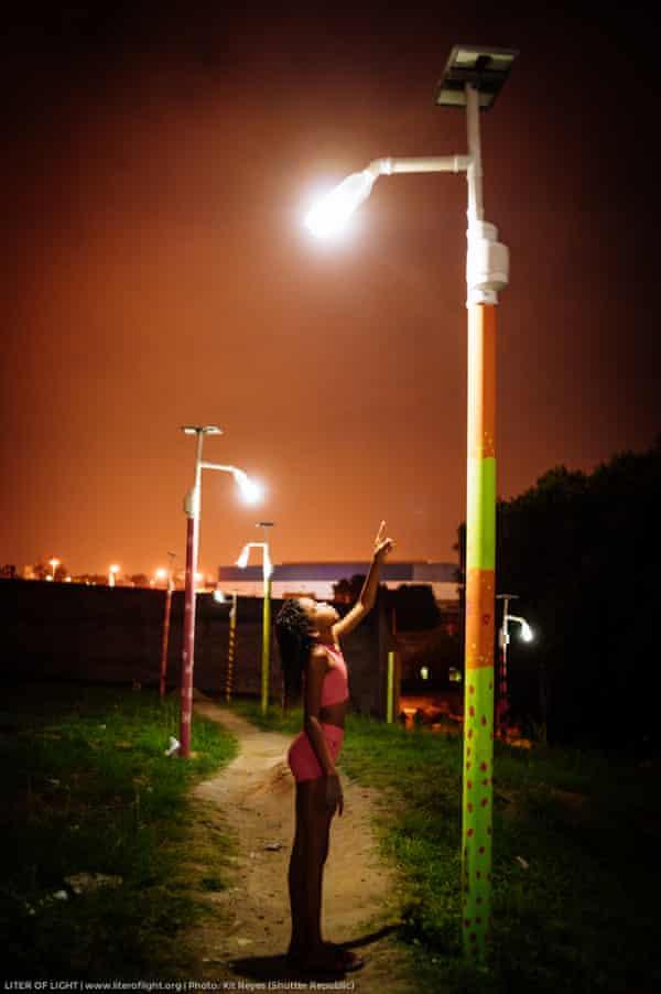 Girl stands under solar powered street light in Rio