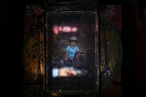 A girl getting her portrait made on a stuffed horse fills the viewfinder of Luis Maldonado's old wooden old box camera