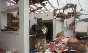 Bob Moore stands in his house in Rowlett, Texas, Sunday, Dec. 27, 2015, the morning after it was damaged by a tornado. At least 11 people died and dozens were injured in apparently strong tornadoes that swept through the Dallas area and caused substantial damage this weekend. (AP Photo/Rex C. Curry)