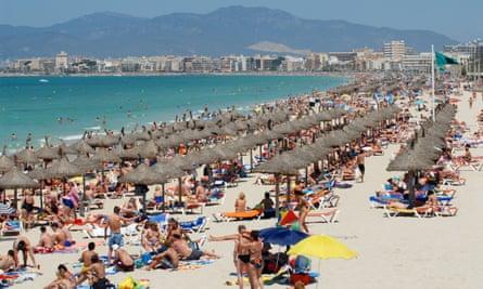 Sunbathers crowd a beach in Mallorca.