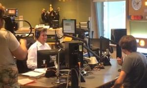 Ed Miliband wearing headphones in a radio studio.