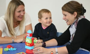 A young boy with two women, receiving therapy using a toy