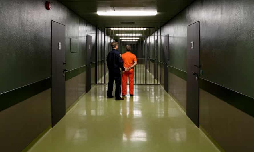 A prison guard leading a prisoner along a corridor