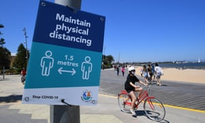 A bike rider near Coronavirus signage on St Kilda beach in Melbourne today