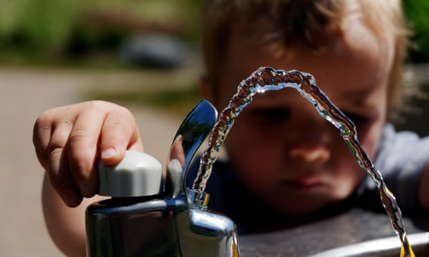 A young boy playing with a drinking water fountain