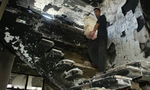 An Iraqi man collects books from destroyed Iraqi National Library in Baghdad, April 17, 2003.