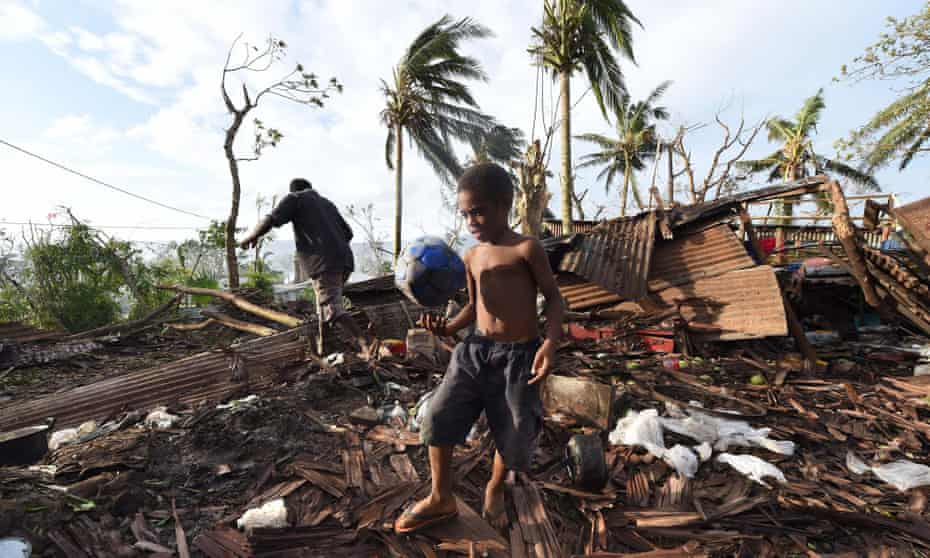 Port Vila residents search through the ruins of their home.