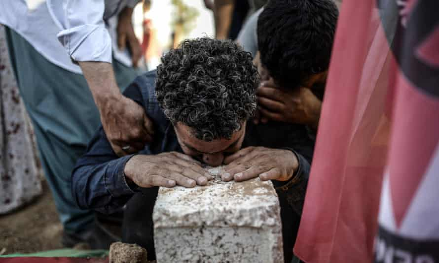 A man mourns during the funeral ceremony of victims of the suicide bomb attack in Suruc
