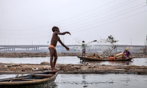 A boy casting his fishing nets in the lagoon by Makoko.