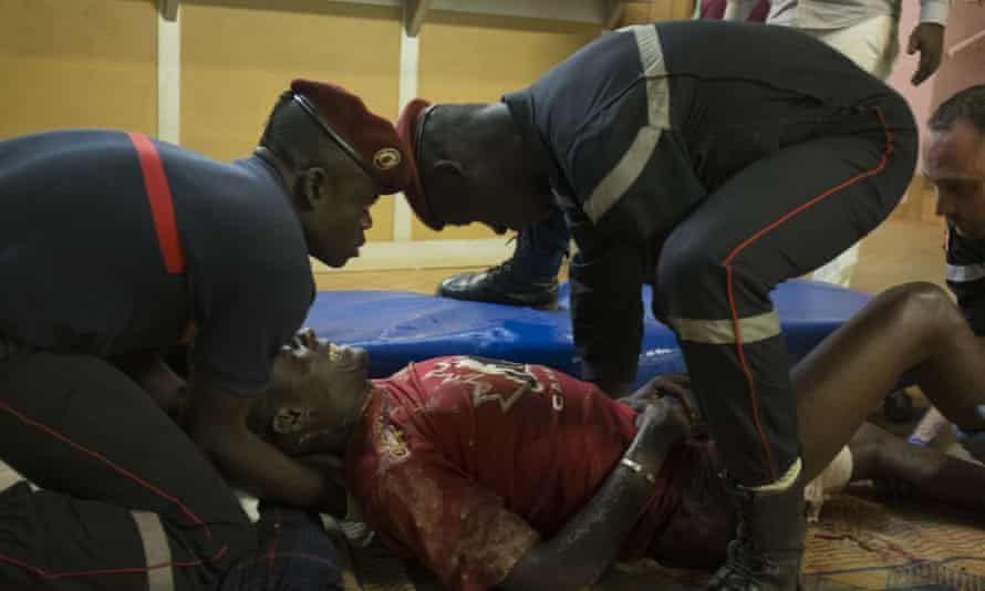 French first responders tend to a man wounded in the attack.