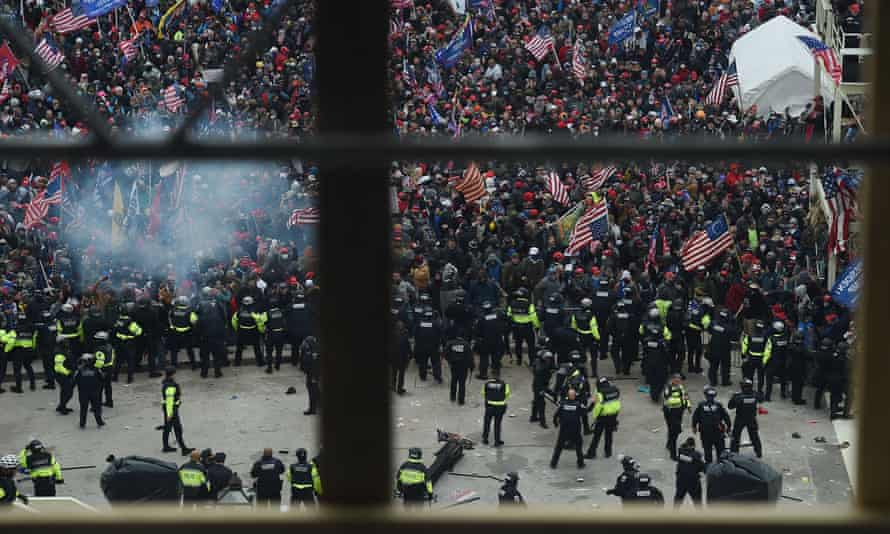 Police hold back a mob gathering outside the US Capitol in Washington DC on 6 January.