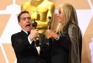 Lee Unkrich and Darla K. Anderson with their awards for Animated Feature for Coco