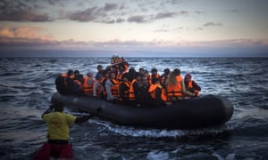 Refugees and migrants arrive on a dinghy from the Turkish coast to the Greek island of Lesbos